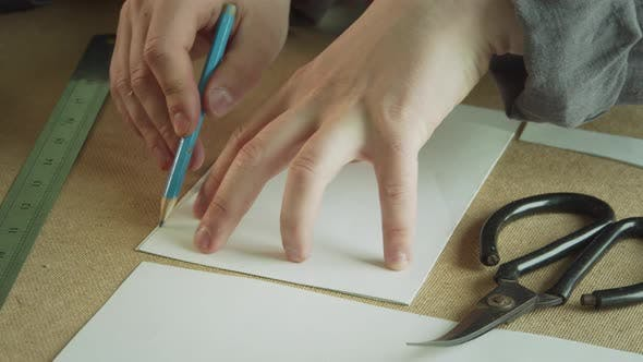 Close-up of Creating Patterns for the Production of Handmade Clothing. A Hand with a Pencil Draws a