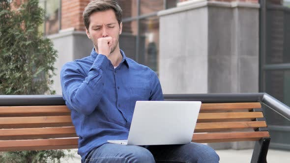 Thumbnail for Sitting Outdoor Young Man Coughing while Working on Laptop