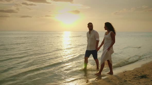 Cover Image for Romantic Couple in Love Walking By the Sea at Sunset