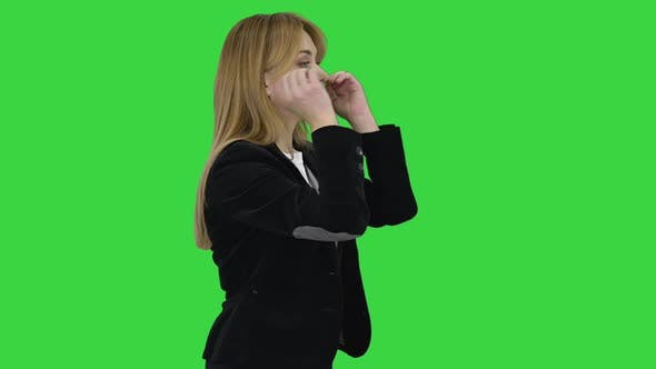 Blonde Business Woman Walking and Touching Her Hair on a Green Screen, Chroma Key.