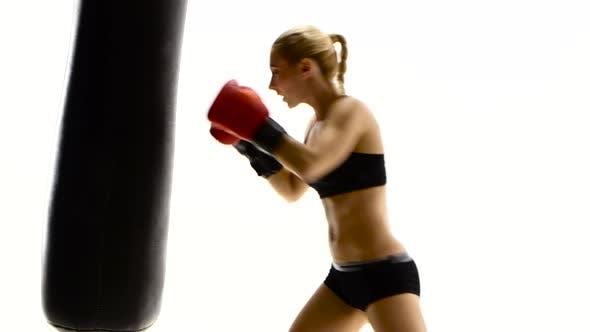 Thumbnail for Kickboxer Woman Fulfills Blows on Punching Bag, White Studio