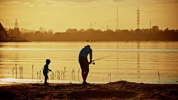 Thumbnail for A Father and His Son in Pair Clothes on Fishing Together - a Man Holding the Rod and Fishing and the