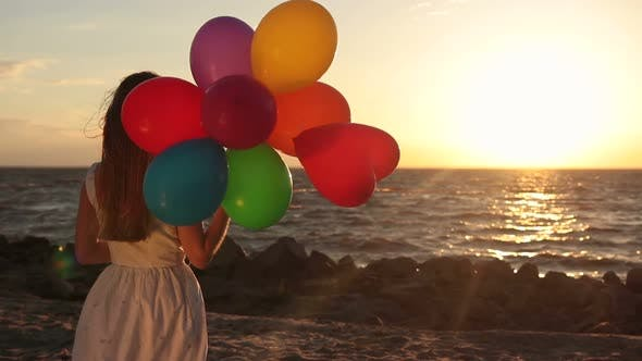 Thumbnail for Girl with Colorful Balloons on Beach at Sunset