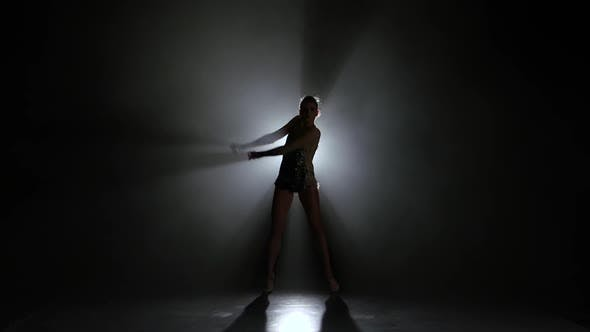 Thumbnail for Girl Gymnast with Mace in Hand Revolve Around Him. Black Background. Light Rear. Silhouette