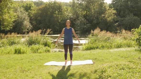 Stretching in park in the morning. Yoga exercises. Woman practicing yoga outdoors.