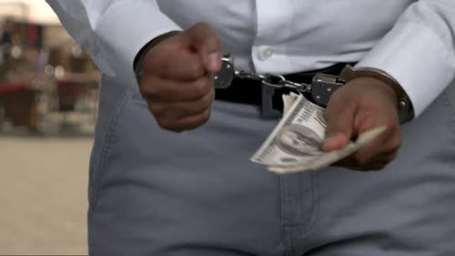 Close Up Man in Handcuffs Holding Money