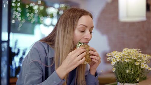 Beautiful Young Blonde Woman Eating a Big Burger in a Fast Food Restaurant
