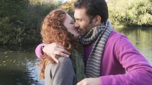 Thumbnail for Couple kissing and hugging by river