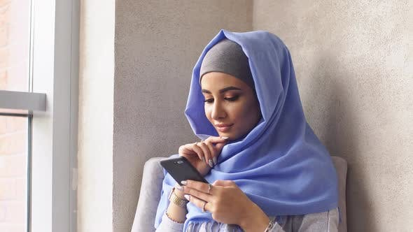 Thumbnail for Modern Muslim Girl in Hijab Holding His Smartphone.