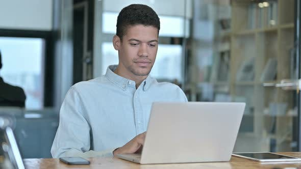 Cover Image for Young African Man Getting Shock on Laptop at Work