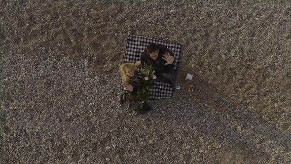 Thumbnail for Woman and Man Sitting on Blanket on Beach, Looking up And Waving, Aerial View