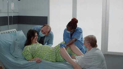 Multi Ethnic Doctor and Nurse Helping with Childbirth