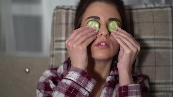 Thumbnail for Portrait of Pretty Young Woman in Pajama Making Eye Mask From Cucumbers in Cozy Evening