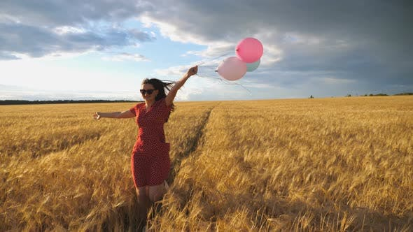 Thumbnail for Young Smiling Woman with Brown Hair Running Through Golden Wheat Field with Balloons