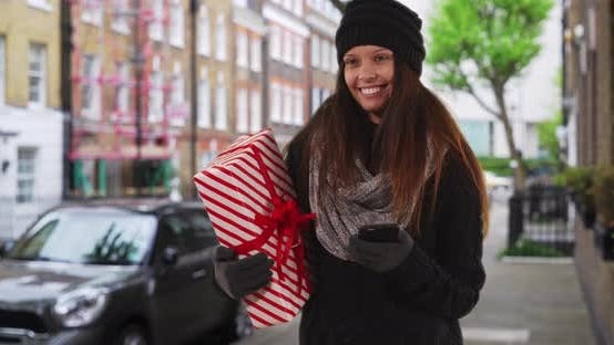Thumbnail for Woman on city street looking around while holding Christmas gift and smartphone