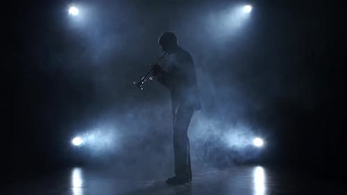 Musician in a Smoky Studio Playing in a Trumpet