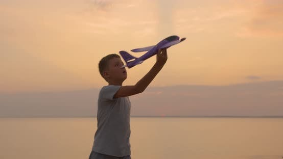 Thumbnail for Happy Kid Playing with Toy Airplane Against Orange Sun Summer. Best Childhood Concept