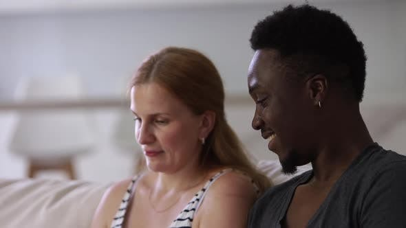 Interracial Couple at Sofa Wbrowsing Tablet