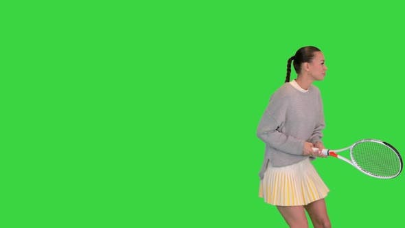 Girl with Tennis Racket Imitating the Game on a Green Screen Chroma Key