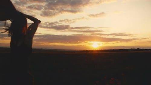 Weibliches Springen in Aufregung.  Sonnenuntergang
