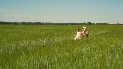 Slow Motion Young Mother Plays with the Child in the Field Dressed in Red Dress The Daughter Goes to