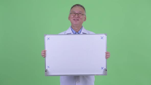 Cover Image for Happy Mature Japanese Man Doctor Thinking While Holding White Board