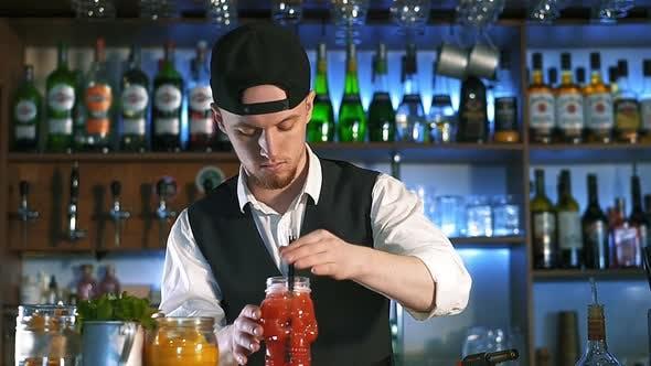 Der Barkeeper bereitet einen alkoholischen Cocktail vor.