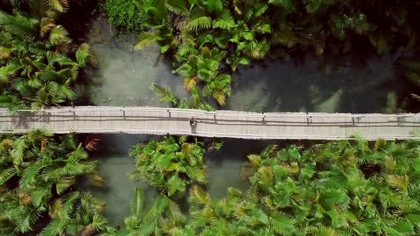 Aerial view of woman walking on long wooden bridge in Bojo river, Philippines.