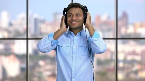 Happy Cheerful Guy Listening To Music in Headphones