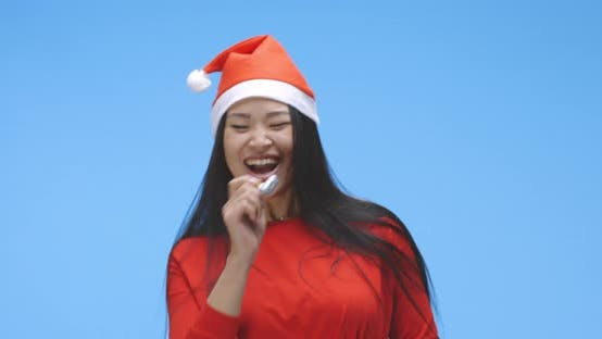 Young Woman Partying in Santa Hat with Party Horn