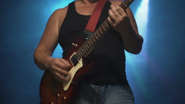 Chubby Male Rocker Musician With Electric Guitar On Stage