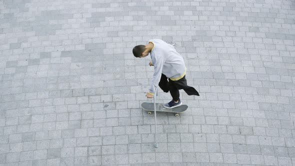 Cover Image for Top View of the Man with One Leg on Crutches Spinning on His Skateboard Doing Tricks