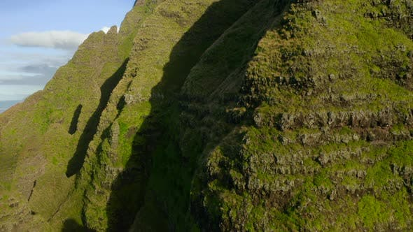 Thumbnail for Grassy Mountain Slope Illuminated with Bright Sun Light, and Ocean Coastline Behind. Aerial Shot