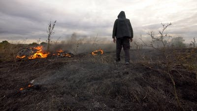 man walks on a burning field in the steppe