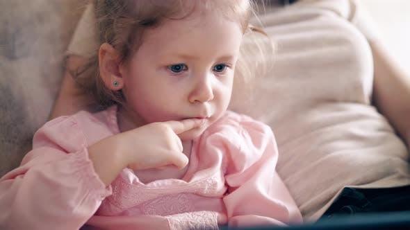 CU,: Jeune mère attrayante et douce fille sont assis sur le canapé et l'entraînement à l'aide d'un