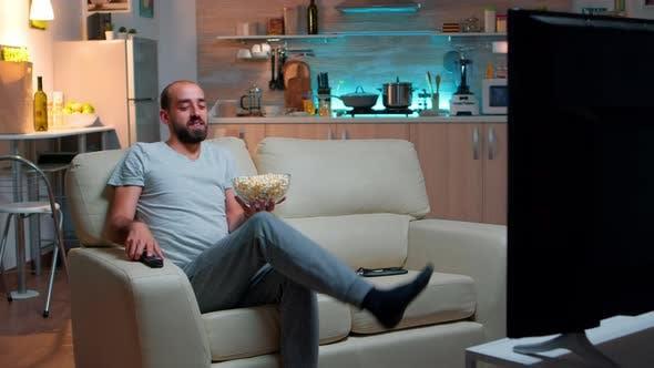 Mann isst Popcorn und schaut fern
