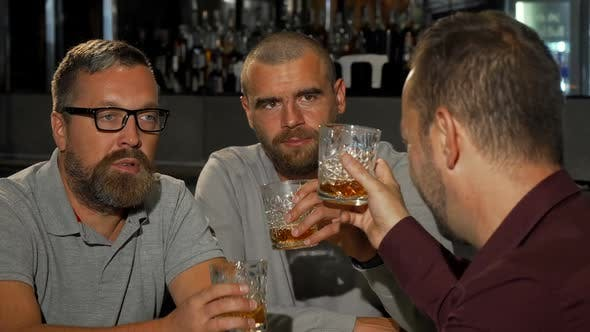Cover Image for Happy Mature Man Smiling To the Camera While Drinking Whiskey with Friends