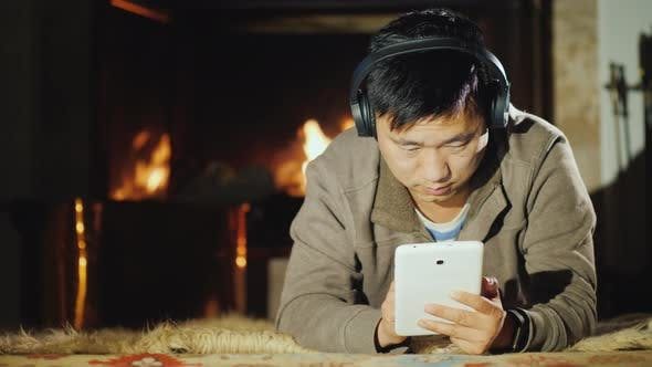 Thumbnail for A Serious Asian Man Uses a Tablet at Home, Lies Near the Fireplace