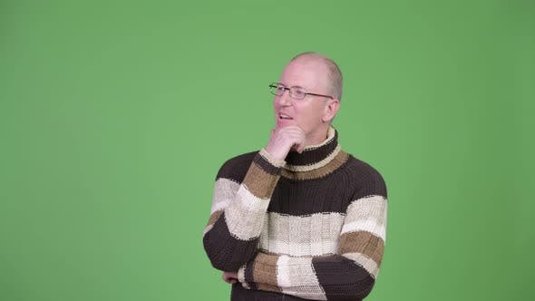 Thumbnail for Happy Mature Bald Man with Turtleneck Sweater Thinking While Looking Up