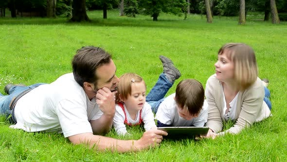 Thumbnail for Family, Middle Aged Couple in Love, Boy and Girl, Lying in Grass and Work on Tablet