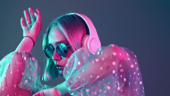 Mysterious Hipster Teenager Listening To Music with Headphones. Portrait of Millennial Pretty Girl