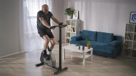 Keeping Fit and Health for Middleaged People During Selfisolation Man Is Training with Exercycle