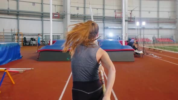 Thumbnail for Pole Vaulting Indoors - a Young Woman Jumping Over a Bar with a Pole