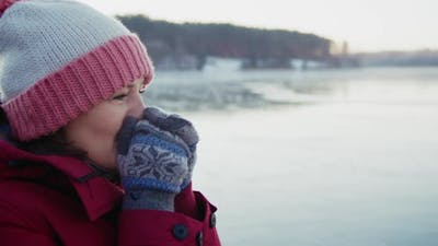a Woman Wearing Mittens Warming Hands with Her Breath