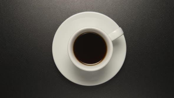 Thumbnail for Weiße Tasse mit Kaffeegetränk dreht sich auf schwarzem Tisch