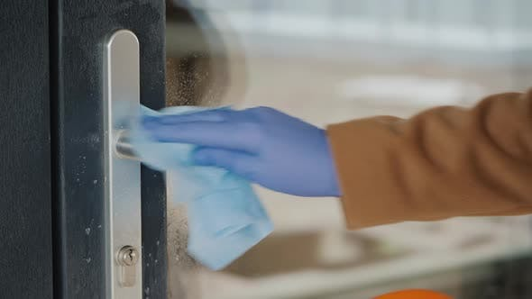 Thumbnail for A Hand in a Protective Glove on the Handle of the Front Door