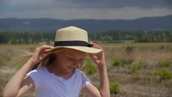Thumbnail for Smiling Teen Girl in Hat Walking on Meadow at Summertime