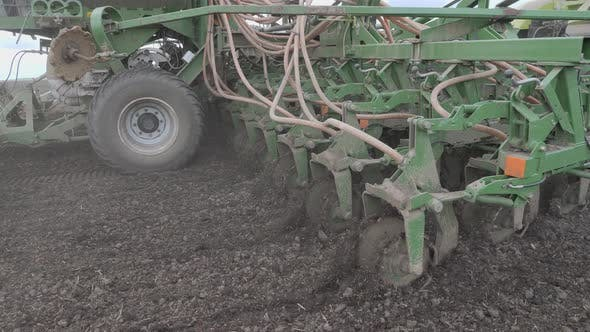 Sowing in the Field. The Seeder Distributes Seeds and Fertilizers Over the Plowed Land. Universal