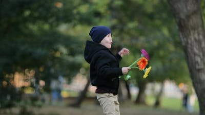 Little Boy is Dancing in a Park with Flowers
