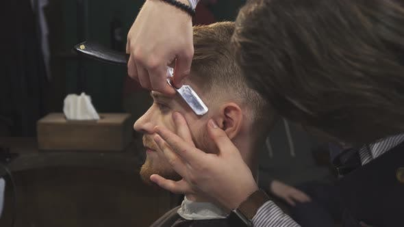 Thumbnail for Handsome Man Getting Shaved with a Razor By a Barber